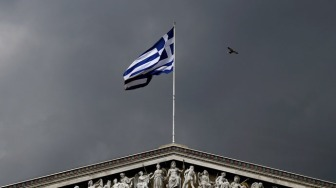A Greek national flag flutters next to statues of ancient Goddess Athena and God Apollo atop the Athens Academy